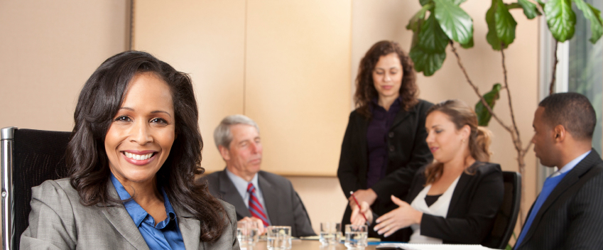 A business woman smiles at the camera while seated at a conference table. Behind her, her colleagues are chatting.