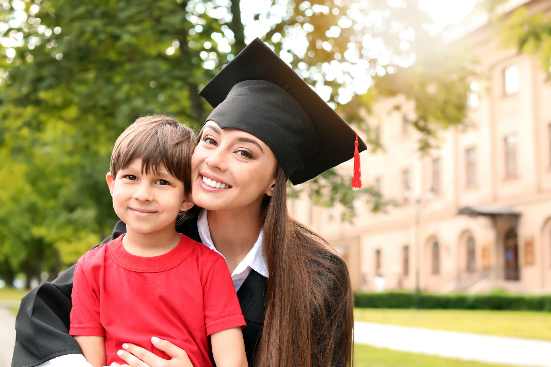 young woman wearing graduation cap and gown, holding young child. Both smile at camera.
