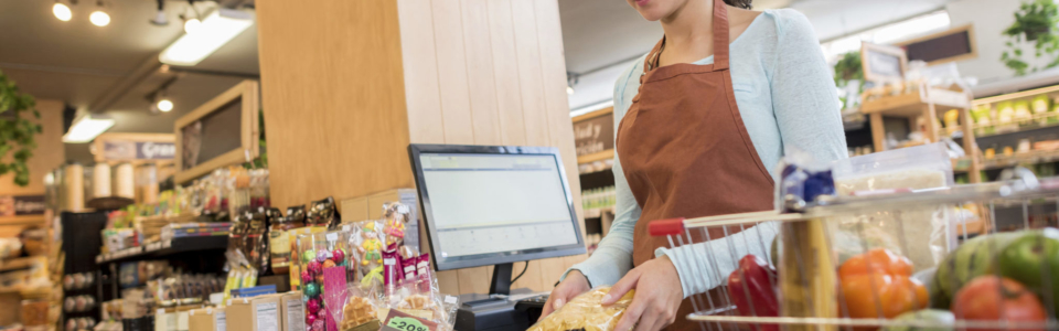 A woman is working as a checker at a grocery store. She wears an apron and is scanning items.