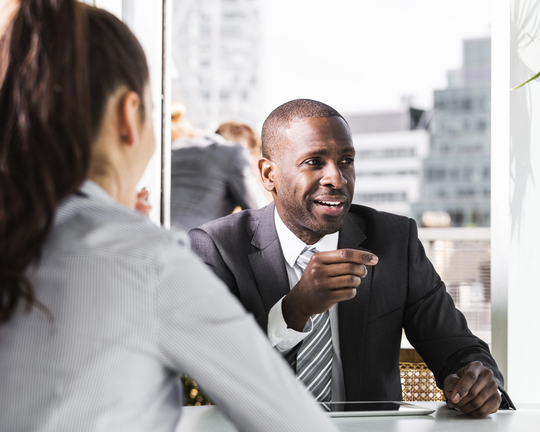 businessman smiles away from camera as he talks to a woman