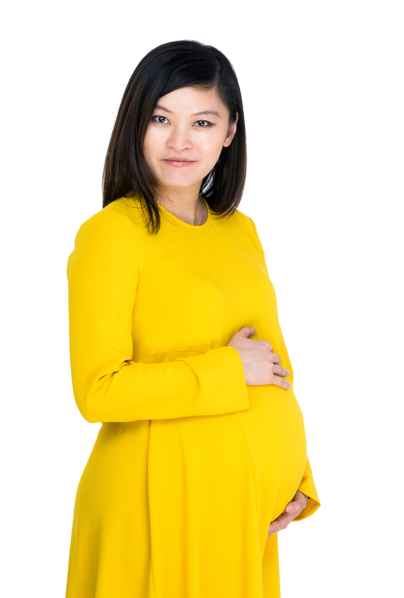 edbb29d47e34d A pregnant woman in a bright yellow dress holds her stomach and smiles at  the camera