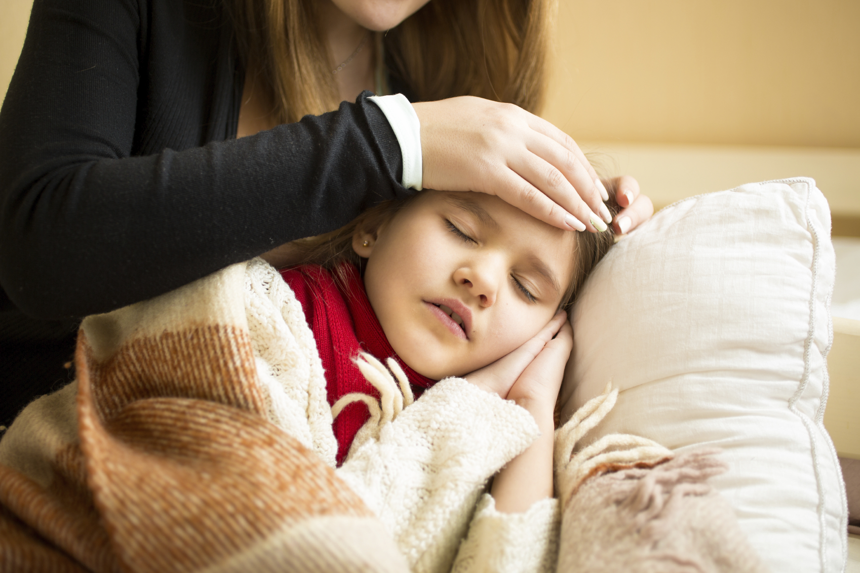 Closeup of caring mother holding head on sick daughter forehead